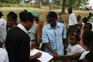 A community health worker registering patients at a rural health fair